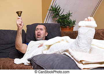 Sick and angry - A man lying with a broken leg on the couch...
