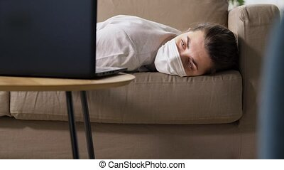 sick bored woman with laptop lying on sofa at home - people...