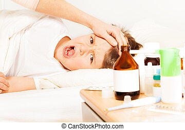 Sick boy crying while mother checking temperature