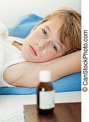 Sick boy laying down next to medicine bottle