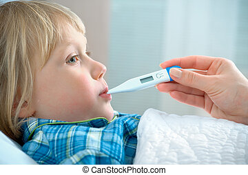 sick boy lying in bed with a thermometer