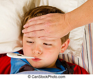 Sick child boy being checked for fever and illness while...