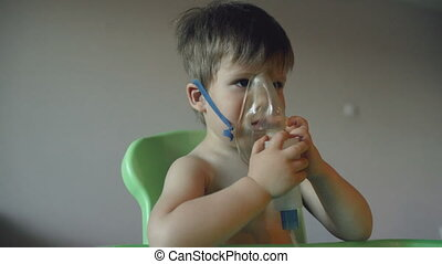 Sick child breathes through nebulizer inhalation, boy with an oxygen mask on his face having treatment at home