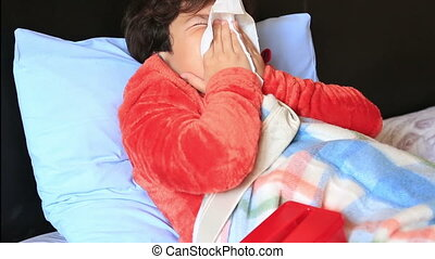 Sick child in bed sneezing