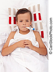 Sick child in bed with thermometer