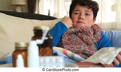 Sick child lying in bed with a thermometer in mouth