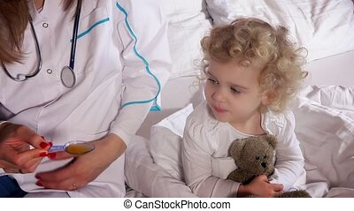 Sick child open mouth and take medicine with female doctor sitting on bed