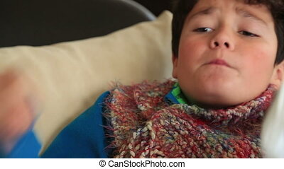 Sick child with a thermometer in mouth sneezing
