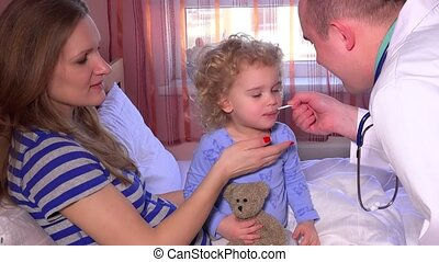 Sick child with mom open mouth and take medicine from male...