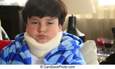 Portrait of a painful little boy with a neck brace looking at the camera and showing thumbs down
