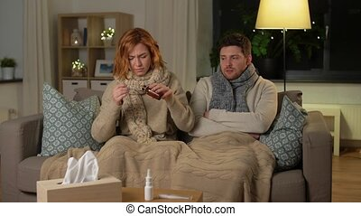 healthcare, people and medicine concept - sick couple with medication or antipyretic syrup and spoon at home