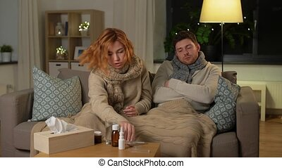sick couple with thermometer and tea at home