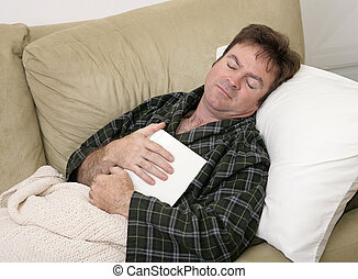 Sick Day - A man home sick from work has fallen asleep while...