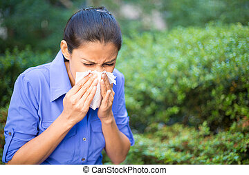 Closeup portrait, young woman in blue shirt with allergy or cold, blowing her nose with a tissue, looking miserable unwell very sick, isolated outside green trees background. Flu season, vaccination.