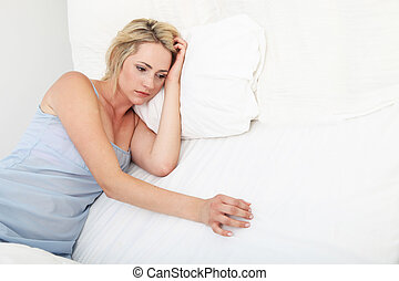 Sick depressed woman lying propped up on her pillows in bed in her nightgown
