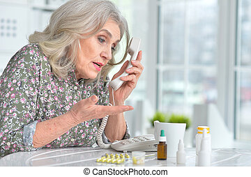 Sick elderly woman calling a doctor