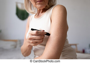 Sick elderly woman measure glucose level at home