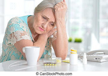 Sick elderly woman with medication