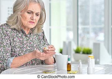 Sick elderly woman with medicines