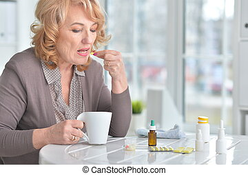 Sick elderly woman with medicines
