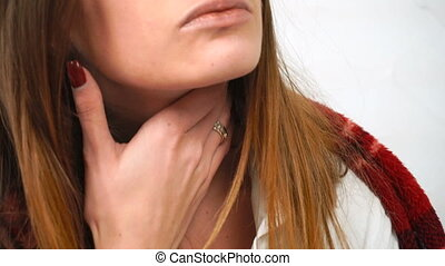 sick girl touches her throat at home