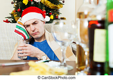 Sick hungover man in Santa hat with glass of water - Sick...
