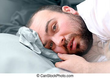 Sick In Bed - a man laying in bed looking like he is sick