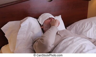 Sick in bed with cold and flu - Man laying in bed coughing...