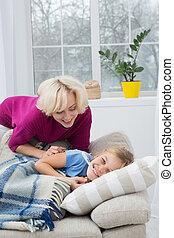 Sick liitle girl lying on sofa at home.