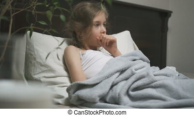 Sick little girl coughing lying in the bed.
