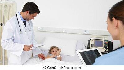 Sick little girl lying in bed talking