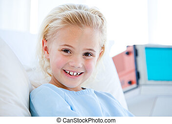 Sick little girl sitting on a hospital bed