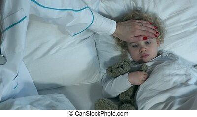 Sick little girl with loved toy lying while nurse doctor taking temperature
