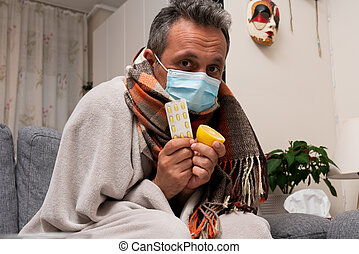 Sick adult male model wearing medical or surgical disposable mask covering neck using colourful scarf presenting lemon for vitaminc immunity and sars covid19 flu cold medical treatment