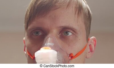 Sick man and oxygen mask portrait eyes closeup unshaven messy male interior