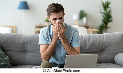 Sick man blowing nose, holding handkerchief, using laptop at home