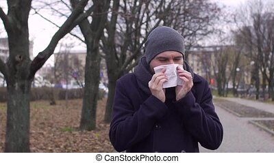 Sick man blowing nose in cold weather, slow motion.