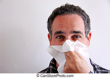 Sick man blowing nose - Man with a flu blowing his nose