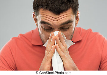 sick man blowing nose to paper napkin at home