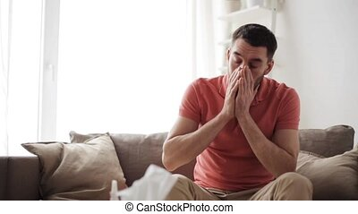 sick man blowing nose to paper napkin at home - healthcare,...