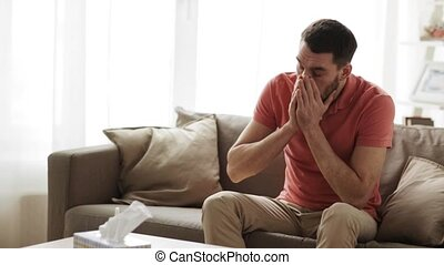 sick man blowing nose to paper wipe at home - healthcare,...