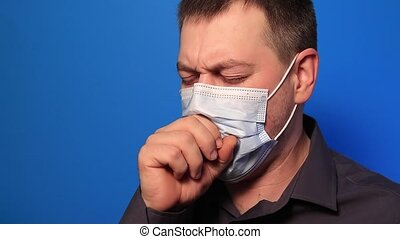 Sick man coughs heavily, hemoptysis hemorrhage spitting blood in saliva as a result of tuberculosis or lung cancer on a blue background. Open tuberculosis or severe pneumonia lung disease.