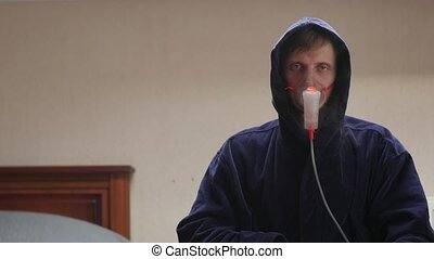 Sick man falling asleep in oxygen mask in hood dark blue bathrobe portrait interior looking at camera