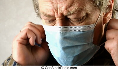 Sick man in medical mask is suffocating, breathing heavily, he does not have enough oxygen. Perhaps he is infected with Covid-19 virus and has panic attack. Close-up portrait. Indoors.
