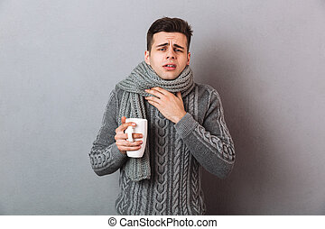 Sick Man in sweater and scarf having a sore throat