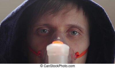 Sick man in the hood oxygen mask dark blue bathrobe treatment eyes closeup portrait interior look into the camera