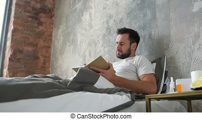 Sick man looking at bottle of eye drops while reading