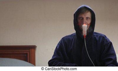 Sick man looks Into camera in oxygen mask in hood dark blue bathrobe portrait interior