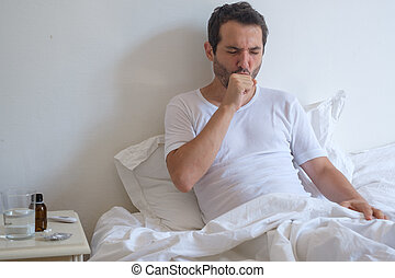 Sick man lying on bed and coughing