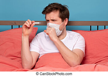 Sick man lying on bed checking his temperature at home.